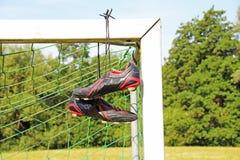 Fußballstiefel, die an einem Fußballbeitrag hängen Stockbild