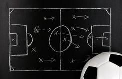 Fußballstrategie auf einer Tafel mit Kugel Stockfotografie
