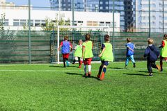 Fußballteam - Jungen im roten und blauen, grünen einheitlichen Spielfußball auf dem grünen Feld Teamspiel, Training, aktiver Lebe lizenzfreies stockfoto
