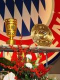 Fußballtrophäen vor Zeichen Bayern-München Stockbilder