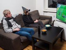 Fußballweltcupfußball des Vaters und des Sohns aufpassender im Fernsehen stockbilder