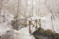 Fußbrücke im schneebedeckten Wald Stockfoto