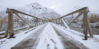 Fußdrucke im Schnee auf einer Brücke, die zu das Dorf, Bessans, Frankreich 2018 führt stockbild