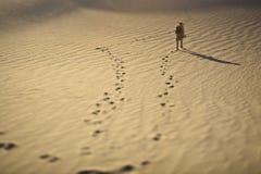 """Fußdrucke und ein Forscher im Sand in der Unschärfeart Schiebephotographie Tilt†"""" Lizenzfreie Stockfotografie"""