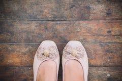 Fußfrauenschuh auf dem hölzernen Hintergrund, stehend auf schmutzigem Boden Stockbilder