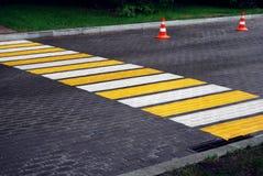Fußgängerübergang- und Verkehrskegel auf nasser gepflasterter Straße stockfotografie