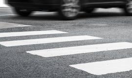 Fußgängerübergangmarkierung und sich schnell bewegendes Auto Lizenzfreie Stockfotografie