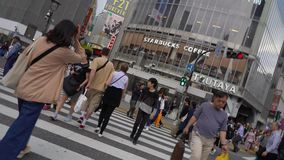 Fußgänger, die auf im Stadtzentrum gelegene Shibuya-Überfahrt gehen stock video footage