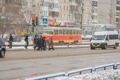 Fußgänger führen schneebedeckte Straße im grünen Licht Stockfotos