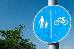 Fußgänger-/Fahrradzeichen gegen blauen Himmel stockbild