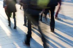Drängen Sie sich auf dem Bürgersteig am Sonnenuntergang mit langen Schatten Lizenzfreie Stockbilder