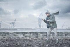 Fußgänger mit einem Regenschirm stellt starken Wind und Regen gegenüber stockbild