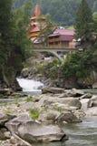 Fußgängerbrücke über einem Wasserfall auf einem Gebirgsfluss Lizenzfreie Stockfotografie