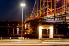Fußgängermetallbrücke mit farbigen Lichtern über dem Fluss lizenzfreie stockfotos