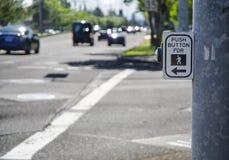 Fußgängerquerwegzeichen und -knopf auf verkehrsreicher Straße mit Autos a Lizenzfreie Stockbilder