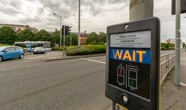 Fußgängerwartezeit-Zeichen an der Pelikanüberfahrt in Englisch und in Wel stockbilder