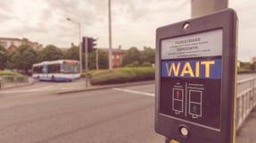 Fußgängerwartezeit-Zeichen an der Pelikanüberfahrt in Englisch und in Wel lizenzfreie stockfotografie