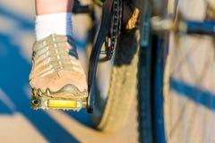 Fußmädchen in den Turnschuhen auf einem Fahrrad Stockfotografie