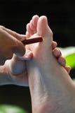 Fußmassage durch hölzernen Stock stockfotografie