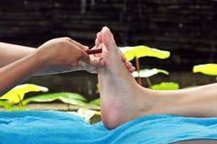 Fußmassage durch hölzernen Stock Stockbilder
