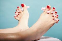 Fußpediküre, die rote Zehennägel auf Blau anwendet Lizenzfreie Stockfotos
