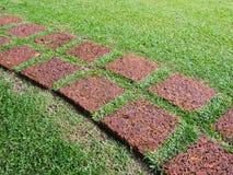 Fußweg hergestellt vom Stein auf grünem Gras Stockfotografie