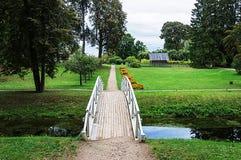 Fußweg im alten Park mit weißer Holzbrücke Lizenzfreie Stockfotografie