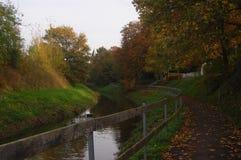 Fußweg nahe bei Nebenfluss im Herbst Lizenzfreies Stockfoto