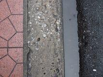 Fußwegengrenze mit Fliese, Zement, Abwasser und gepflasterter Straße Stockfotos