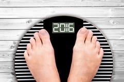 2016 Fuß auf einer Gewichtsskala auf weißem Bretterboden Lizenzfreie Stockfotografie