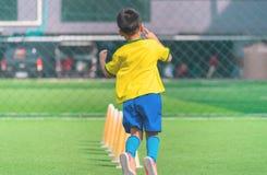 Fu?ball-Junge, der allein mit Kegel auf ?bungsfeld ausbildet lizenzfreies stockbild