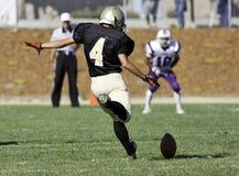 Fußball-Spieler, der einen Ball tritt Lizenzfreies Stockfoto
