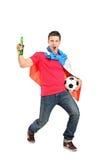 Fußballfan, das ein Bier und einen Fußball anhält Lizenzfreie Stockfotos