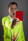Fußballreferent im gelben Hemd, welches die rote Karte zeigt Stockfotos