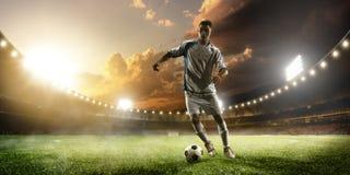 Fußballspieler in der Aktion auf Sonnenuntergangstadions-Panoramahintergrund Stockfoto