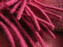 Fuchsia fringe cascading over folded wool scarf. Close up of fuchsia fringe over scarf from Ireland. One hundred percent wool. Horizontal shot Stock Image