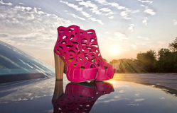 Fuchsia shoes on car and sunset Royalty Free Stock Images