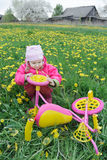 Fuchsiakleurig kleurenjonge geitjes trike met gele wielen en weinig peutermeisje die voertuig onderzoeken Stock Afbeelding
