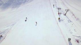 Fucilazione aerea dallo sci della gente del fuco di volo e snowboard sul pendio della neve nella stazione sciistica di inverno El archivi video