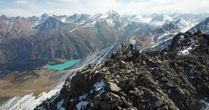 Fucilazione con il fuco Sorvolare le montagne rocciose Gli scalatori hanno scalato alla cima del picco video d archivio