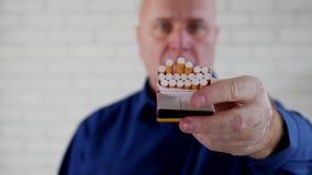 Fucilazione con l'uomo che dà ad un altro fumatore una sigaretta da un nuovo pacchetto archivi video