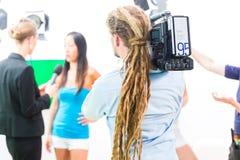 Fucilazione del cineoperatore con la macchina fotografica sull'insieme del film Immagini Stock Libere da Diritti