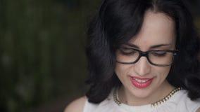 Fucilazione del primo piano dei messaggi sorridenti della lettura del fronte della donna all'aperto video d archivio