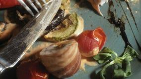 Fucilazione del primo piano: pollo cotto in bacon con le verdure, con salsa ed insalata verde su un piatto blu archivi video
