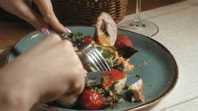 Fucilazione del primo piano: pollo cotto in bacon con le verdure, con salsa ed insalata verde su un piatto blu video d archivio