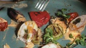 Fucilazione del primo piano: pollo cotto in bacon con le verdure, con salsa ed insalata verde su un piatto blu stock footage