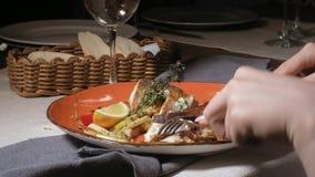 Fucilazione del primo piano: salmone cotto con le spezie, le patate fritte e una fetta di limone su un piatto arancio archivi video