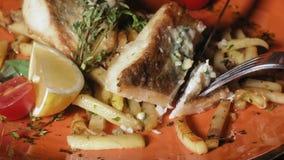 Fucilazione del primo piano: salmone cotto con le spezie, le patate fritte e una fetta di limone su un piatto arancio stock footage