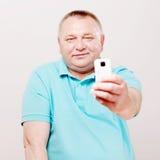 Fucilazione dell'uomo senior sullo smartphone sopra bianco Fotografia Stock