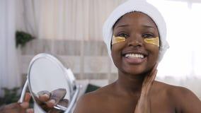 Fucilazione della donna africana giovane attraente con le toppe dorate mediche sotto gli occhi, condizione sorridente del ritratt archivi video